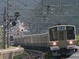 カーブの古虎渓駅を通過する快速電車