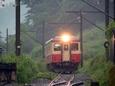 雨煙る南小谷駅に進入する普通列車