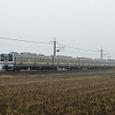 雨の田園地帯を走る普通電車